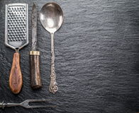 Utensili della cucina su un fondo della grafite Immagine Stock