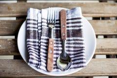 Utensili di legno sul piatto bianco con l'asciugamano di cucina Fotografia Stock