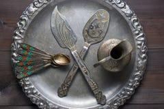 Utensilio de plata retro de la cocina con los ornamentos en la bandeja de plata Foto de archivo libre de regalías
