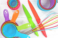 Utensilios coloridos de la cocina en el fondo rústico blanco Imagen de archivo