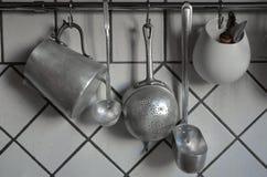 Utensilios coocking de la lata que cuelgan en cocina Foto de archivo libre de regalías