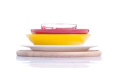 Utensilios de diversos colores que se colocan en un aislante de la tabla de cortar Fotografía de archivo