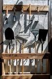 Utensilios de jardinería del metal de la granja como las palas y rastrillos que cuelgan en la pared fotografía de archivo libre de regalías