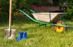 Utensilios de jardinería en un césped verde Pala y botas de goma Imagen de archivo libre de regalías