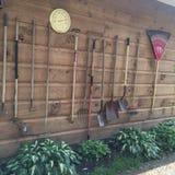 Utensilios de jardinería en una pared de madera resistida Foto de archivo libre de regalías