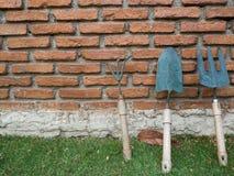 Utensilios de jardinería sobre las paredes de albañilería Fotos de archivo