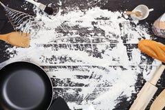 Utensilios de la cocina con la cuchara de madera en la tabla y la harina de madera negras Fotos de archivo