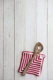 Utensilios de la cocina: Cuchara y Potholder de madera en el CCB de madera blanco Foto de archivo