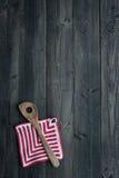 Utensilios de la cocina: Cuchara y Potholder de madera en la parte posterior de madera oscura Imagenes de archivo