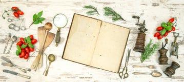 Utensilios de la cocina del vintage con el libro de cocina, las verduras y las hierbas viejos Imágenes de archivo libres de regalías