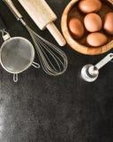 Utensilios de la cocina e ingredientes de la hornada: huevo y harina en fondo negro Fotografía de archivo libre de regalías