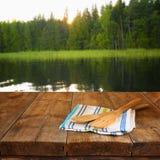 Utensilios de la cocina en mantel en la tabla de madera de las texturas contra fondo otoñal del bosque Fotos de archivo libres de regalías