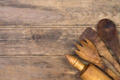 Utensilios de madera de la cocina en fondo de madera Foto de archivo