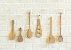 Utensilios de madera de la cocina en la pared de ladrillo blanca Fotografía de archivo