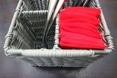 Utensilios de servicio de la cocina en una cesta de mimbre con las bifurcaciones y los cuchillos en la tabla imagen de archivo libre de regalías