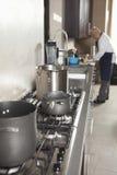 Utensilios en estufa con el cocinero Working In Background Imágenes de archivo libres de regalías