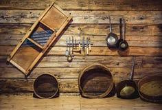 Utensilios tradicionales viejos que cuelgan en la pared de madera en la cocina Fotografía de archivo