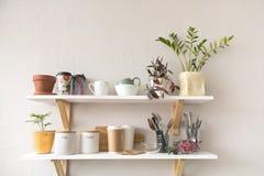 Utensilios y tazas en estante imagen de archivo libre de regalías