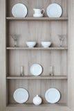 Utensilios y vidrios de la cocina en una pared gris Imagenes de archivo