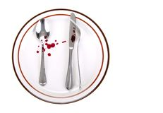 Utensils Crime Scene. An odd position of spoon and knife and fork touch each other on a dinner plate. crime-scene-like setup Stock Photo