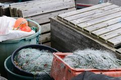 Utensils of a fisherman with nets, boxes and buoys. Stored in wooden boxes and plastic barrels royalty free stock photo