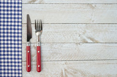Utensils and Gingham on Boards with Copy Space. Red fork and knife with blue gingham cloth on rough white wooden plank background with space for copy Stock Images