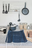 Utensils hanging on the wall with blue apron Stock Image