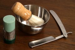 Utensils for shaving. Closeup of an open razor with shaving brush, soap dish and shaving soap stock image