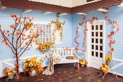 Uteplats i höstsäsong Tak som täckas med tegelplattor, blå vägg arkivbild
