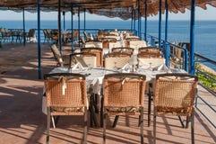 Uteplats som äter middag på en lyxig restaurang som förbiser havet Royaltyfria Bilder