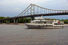 Utfärdskeppet simmar för att down floden nära en bro arkivfoto