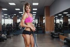 Utför den härliga kvinnan för kondition övning med expanderen i idrottshall S royaltyfria bilder