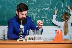 Utföra ett experiment Lärare och elev Manlig lärare som ger kurs i vetenskapsklassrum Allmänhet eller privatskola arkivfoton