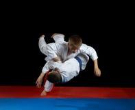 Utföra kast med att falla utbildar idrottsman nen i karategi royaltyfri foto