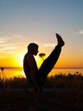 Utförande asana för man på solnedgången Arkivbild