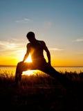 Utförande asana för man på solnedgången Fotografering för Bildbyråer
