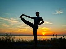 Utförande asana för man på solnedgången Royaltyfri Fotografi