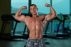 Utförande Front Double Biceps Pose In för kroppsbyggare idrottshall royaltyfri fotografi