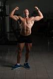 Utförande Front Double Biceps Pose In för kroppsbyggare idrottshall royaltyfri bild