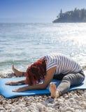 Utförande joga för kvinna på havskust Royaltyfri Fotografi
