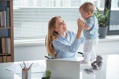 Utgående affärskvinna som har gyckel med ungen Royaltyfri Foto