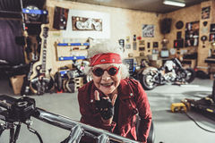 Utgående kvinnlig pensionär som lokaliserar på cykeln arkivfoto