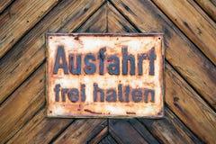 UTGÅNG fria GermanSign på bakgrund för timmervägg Arkivfoto