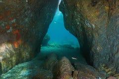Utgången av en nedanför passage vaggar det undervattens- havet royaltyfria foton
