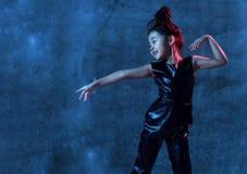 Utgör den asiatiska modellflickan för högt mode i blåa för färgrikt ljust neon färgrika uv och purpurfärgade ljus royaltyfria foton