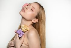 Utg?r den blonda flickan f?r v?ren med st?ngda ?gon som rymmer blommor i h?nder n?ra framsidan, perfekt hud som ?r naturlig, stud royaltyfria bilder