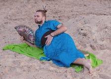Utgör den stiliga mannen för transsexuellen med, hårbullen som ligger på sand i blå kimono och att ge kyssen som rymmer handfanen arkivfoton