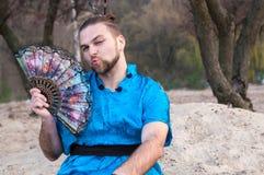 Utgör den stiliga mannen för transsexuellen med, hårbullen som sitter på sand i blå kimono royaltyfri fotografi