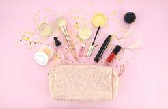 Utgör påsen och uppsättningen av yrkesmässiga dekorativa skönhetsmedel, makeuphjälpmedel och tillbehören på rosa bakgrund Skönhet Arkivbilder