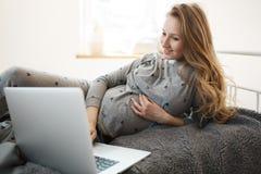 Utgifterhavandeskapperiod med glädje Den härliga blonda unga gravida kvinnan i väl till mods hem beklär att ligga på säng som ser Fotografering för Bildbyråer